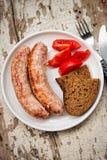 Salsichas grelhadas branco com tomates e pão de mistura Imagens de Stock