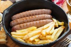 Salsichas grelhadas com batatas fritas em uma frigideira Fotografia de Stock Royalty Free