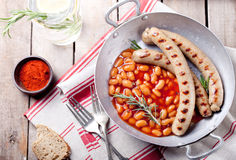 Salsichas grelhadas com os feijões no molho de tomate Foto de Stock
