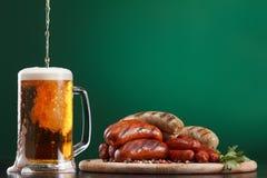 Salsichas grelhadas com vidro da cerveja Imagens de Stock