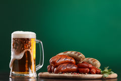 Salsichas grelhadas com vidro da cerveja Fotos de Stock Royalty Free