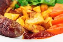 Salsichas grelhadas da carne com batatas fritadas, os tomates cortados, os produtos frescos e a ketchup na placa, foco seletivo foto de stock royalty free