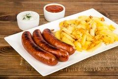 Salsichas grelhadas e batatas fritadas na placa branca na superfície rústica Fotos de Stock Royalty Free