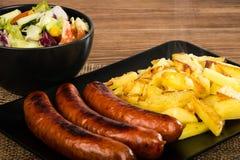 Salsichas grelhadas e batatas fritadas na placa preta na superfície de madeira rústica Imagens de Stock