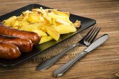 Salsichas grelhadas e batatas fritadas na placa preta na superfície de madeira rústica Imagem de Stock Royalty Free