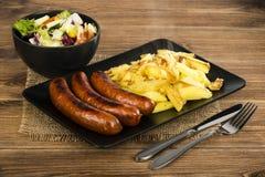 Salsichas grelhadas e batatas fritadas na placa preta na superfície rústica Imagens de Stock