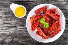 Salsichas grelhadas em um prato branco, vista superior Foto de Stock