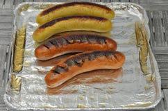 Salsichas grelhadas na grade Fotos de Stock