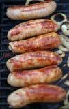 Salsichas na grade com cebolas Imagens de Stock Royalty Free