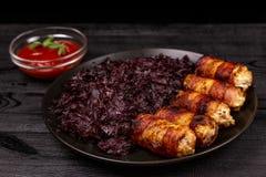 Salsichas ou chevapchichi grelhado caseiro fritado com molho cozido do chucrute e de tomate em um fundo r?stico de madeira fotografia de stock
