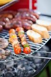 Salsichas, pão e shashliks na grade Fotografia de Stock