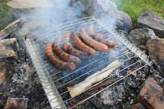 Salsichas que cozinham sobre uma grade aberta do carvão vegetal Fotos de Stock Royalty Free