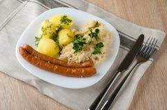Salsichas Roasted com o chucrute cozinhado da couve Fotos de Stock Royalty Free