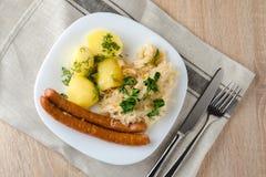 Salsichas Roasted com o chucrute cozinhado da couve e as batatas fervidas Imagens de Stock