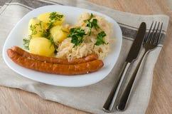 Salsichas Roasted com o chucrute cozinhado da couve e as batatas fervidas Foto de Stock