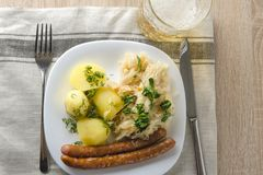 Salsichas Roasted com o chucrute cozinhado da couve e as batatas fervidas Imagem de Stock