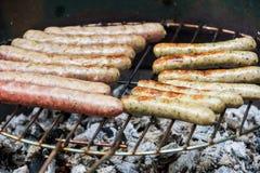 Salsichas saborosos múltiplas na grade no fim acima foto de stock