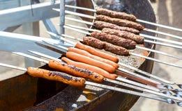 Salsichas saborosos que cozinham sobre os carvões quentes em um assado fotos de stock royalty free
