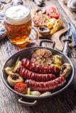 Salsichas Salsichas da grade A salsicha grelhada com cerveja cresce rapidamente tomates e cebolas do alho Fotos de Stock