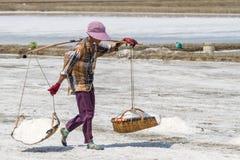 Salt bära för fältarbetare som är salt med den traditionella skuldrapolen med korgar under salt skörd Royaltyfri Foto
