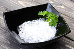 Salt in black bowl on wooden table Royalty Free Stock Photography