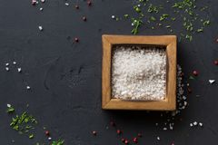 Salt in box on dark background, top view, copy space Royalty Free Stock Images