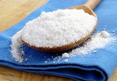 Salt in a brown wooden spoon Royalty Free Stock Photo