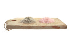 Salt in a chopping board. Piles of rose e black salt in a chopping board royalty free stock image
