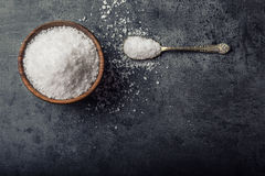 Salt. Coarse grained sea salt on granite - concrete  stone background with vintage spoon and wooden bowl Stock Images