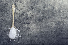 Salt. Coarse grained sea salt on granite - concrete  stone background with vintage spoon and wooden bowl Stock Image
