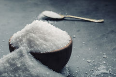 Salt. Coarse grained sea salt on granite - concrete  stone background with vintage spoon and wooden bowl Royalty Free Stock Images
