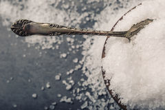 Salt. Coarse grained sea salt on granite - concrete  stone background with vintage spoon and wooden bowl.  Royalty Free Stock Photography