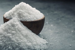 Salt. Coarse grained sea salt on granite - concrete  stone background with vintage spoon and wooden bowl.  Stock Image