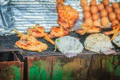 Salt coated tilapia fish that grilled on charcoal stove. Grilled chicken in bamboo stick and grilled eggs for sale. Street food st stock photos