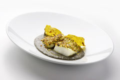 Salt cod crusted with pistachios and black polenta Royalty Free Stock Images