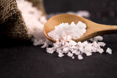 Salt crystals on black stone plate background , selective focus Royalty Free Stock Images
