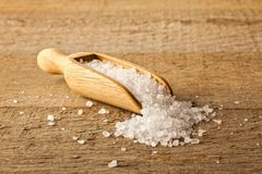 Salt Crystals in a Scoop. A small wooden scoop filled with salt crystals which are spilling onto a rustic wooden surface Royalty Free Stock Image