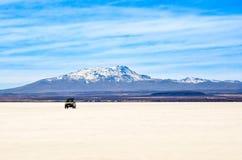 Salt Desert, Uyuni, Bolivia. Panorama- a car crossing the Salt Flats Stock Photos