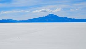 Salt Desert, Uyuni, Bolivia. Panorama of the Salt Flats crossed by cars Royalty Free Stock Photo
