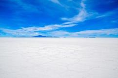 Salt Desert, Uyuni, Bolivia. Panorama  of the Salt Flats with mountain background Royalty Free Stock Photo