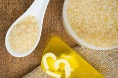 Salt för bad i en stor krus, en vit sked och en gulingtvålstång arkivfoton