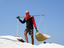 Salt field worker carrying salt with traditional shoulder pole Royalty Free Stock Photo