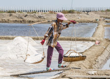 Salt field worker carrying salt with traditional shoulder pole with baskets during salt harvest. In Ban Laem, Thailand royalty free stock photo