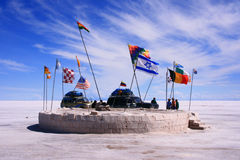 Salt flat museum world flag monument. Salar de uyuni, bolivia, salt flat museum world flag monument, with 4x4 cars and people behind Royalty Free Stock Photo