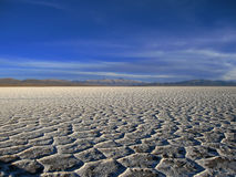 Salt flats. The vast salt flats of Salinas Grandes, Salta, Argentina, stretch across the picture with the blue sky and some mountains in the background royalty free stock photos