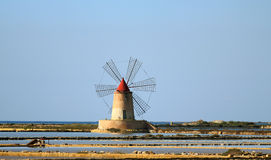 Salt flats and mill. Old windmill in the province of Marsala Royalty Free Stock Photo
