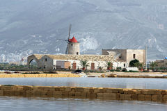 Salt flats and old windmill. Old windmills in the province of Trapani - Sicily Stock Photo