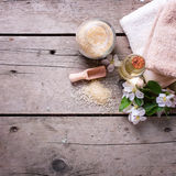 Salt hav, handdukar, aromolja i flaskor och blommor på trälodisar arkivfoto