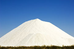 Salt hill heap in Portugal. Heap of sea salt in a marsh with clear blue sky. Location in Algarve, Portugal Stock Images