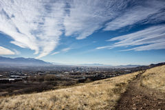 Salt Lake City with sky and path. The skyline of salt lake city is dwarfed by the sky and mountains in the background. A trail curves through the foreground Stock Image
